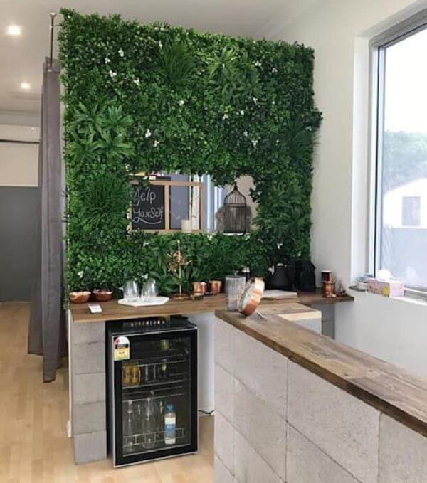 O jardim vertical artificial fixado na parede traz aconchego a todos que utilizam o ambiente da copa