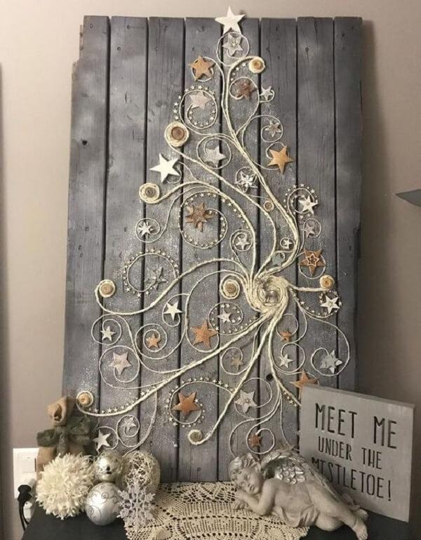 Árvore de Natal na parede feita com estrutura de madeira