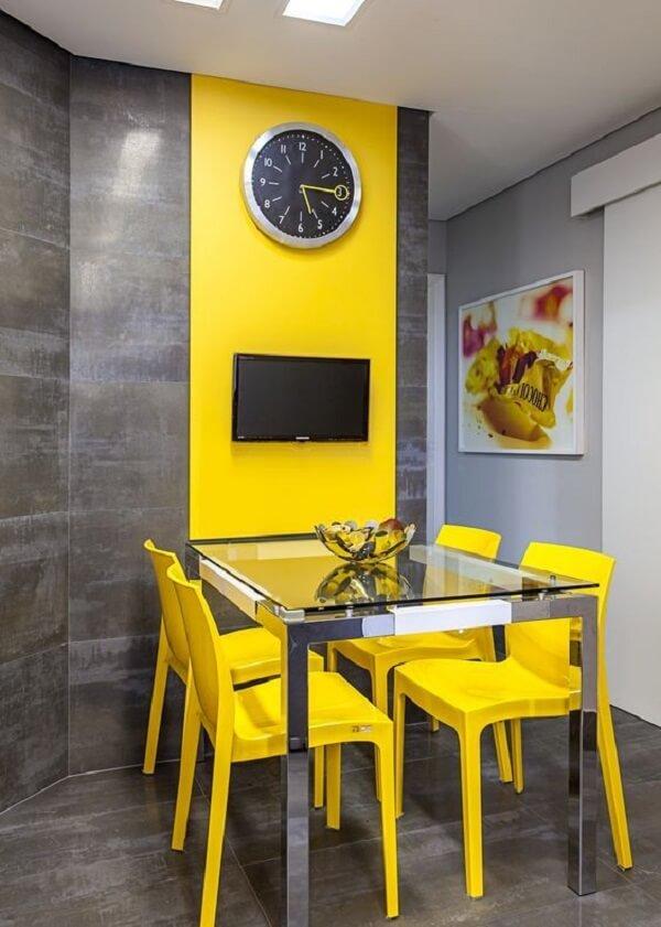 A cadeira amarela segue o mesmo tom do revestimento da parede