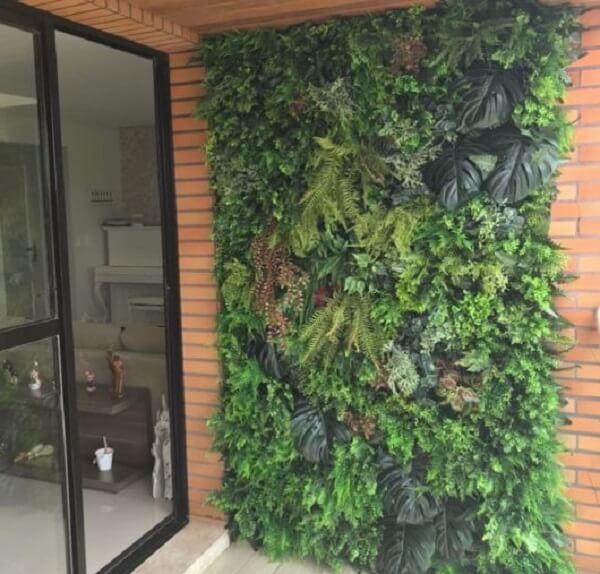 A entrada desse prédio recebeu uma parede revestida com jardim vertical artificial
