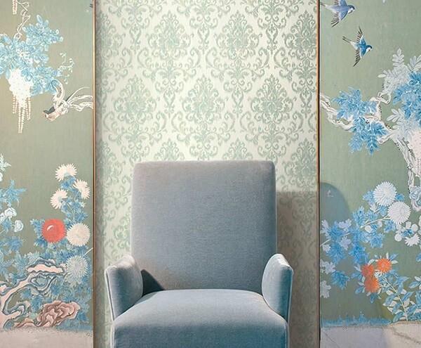 A neutralidade da poltrona cinza claro se harmoniza perfeitamente com o papel de parede