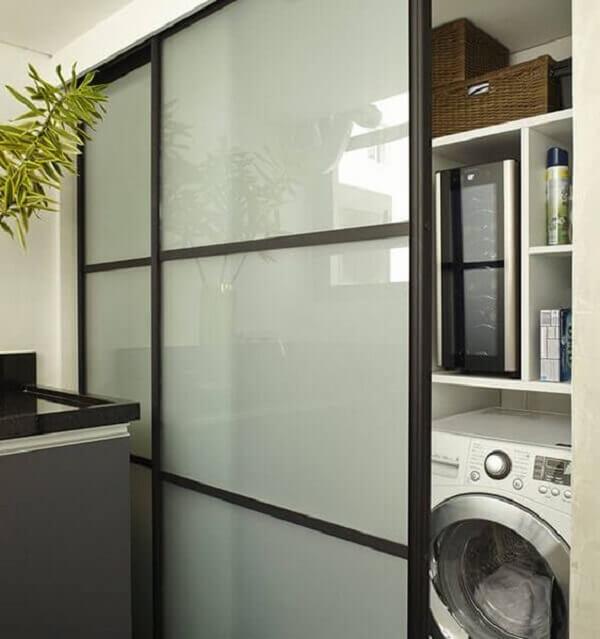 A porta com vidro jateado foi utilizada para esconder a lavanderia no ambiente