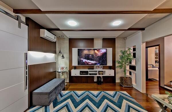 Ambiente amplo com puff baú cinza e tapete geométrico colorido