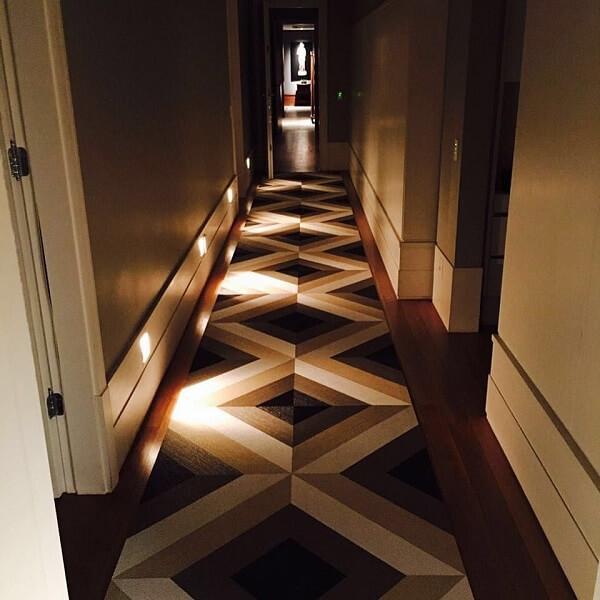 Ambiente com luminárias de piso e tapete geométrico retangular