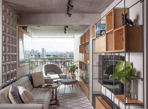 Ambiente compacto decorado com estante metálicas e poltrona cinza claro
