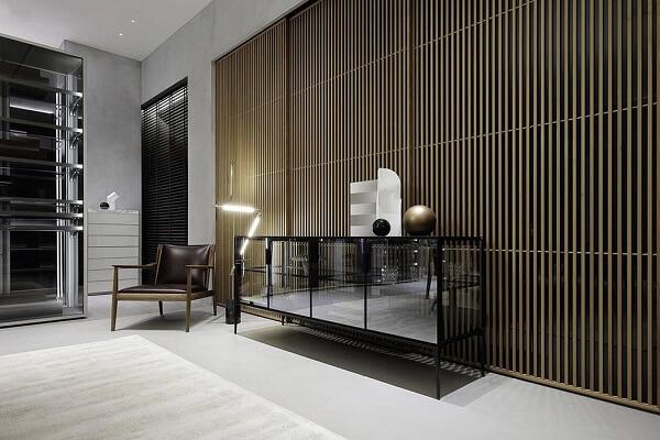 Ambiente decorado com aparador, cadeira de couro e parede de cimento queimado