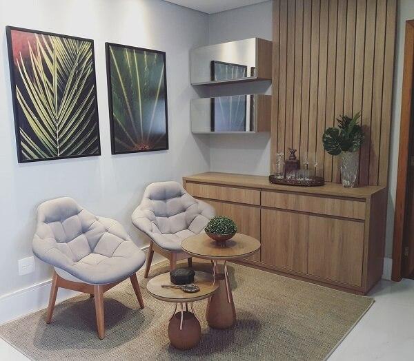 Ambiente decorado com aparador de madeira e poltrona cinza claro