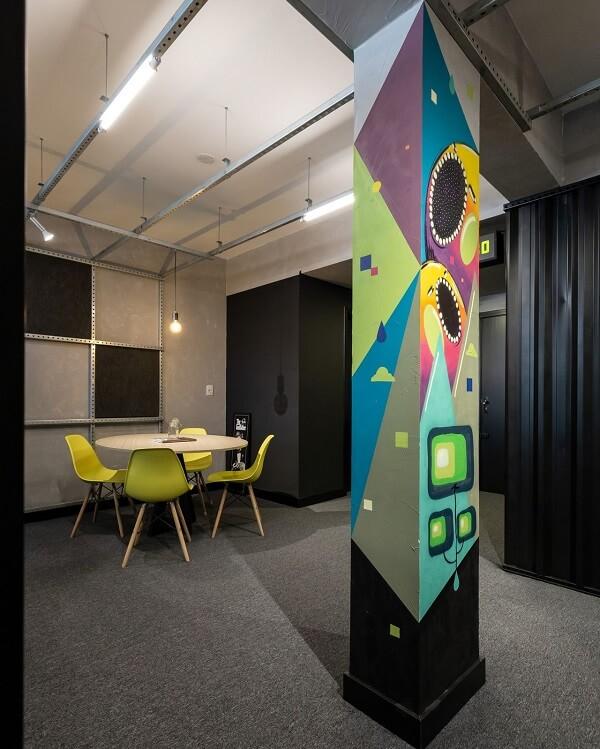 Ambiente decorado com parede de cimento queimado e piso de carpete