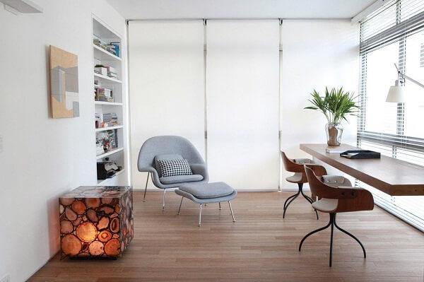 Ambiente decorado com poltrona cinza e mesa suspensa de madeira