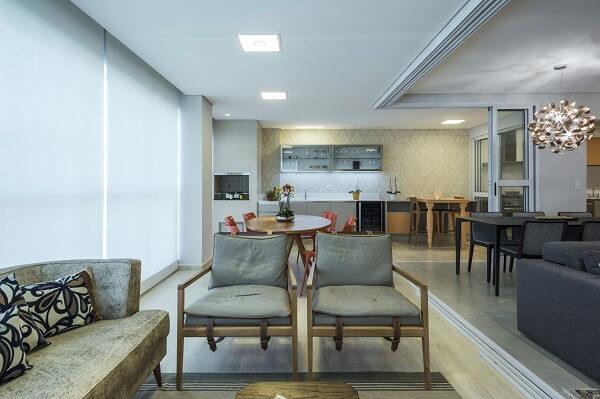 Ambiente integrado decorado com poltrona cinza e almofadas estampadas