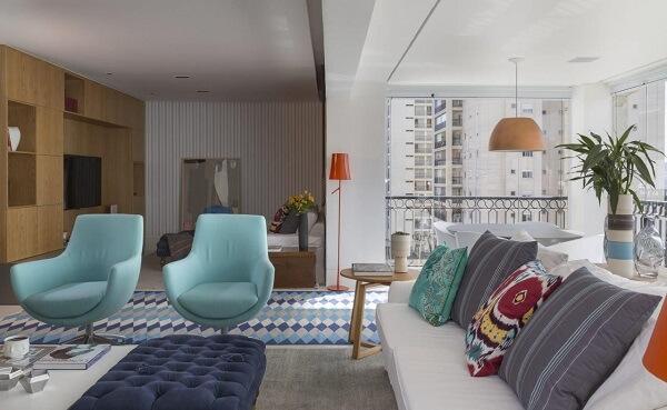 Apartamento compacto com pendente de cobre e tapete geométrico em tons de azul