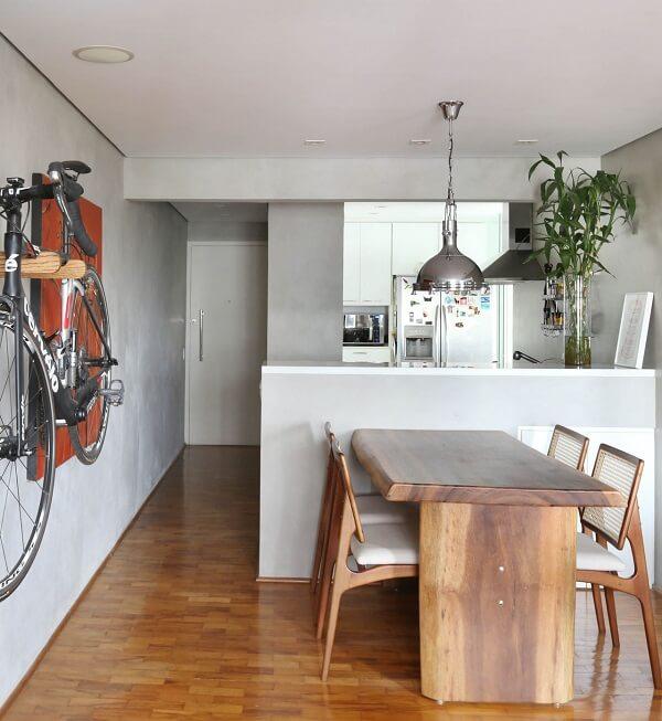 Apartamento decorado com mesa de madeira e parede de cimento queimado