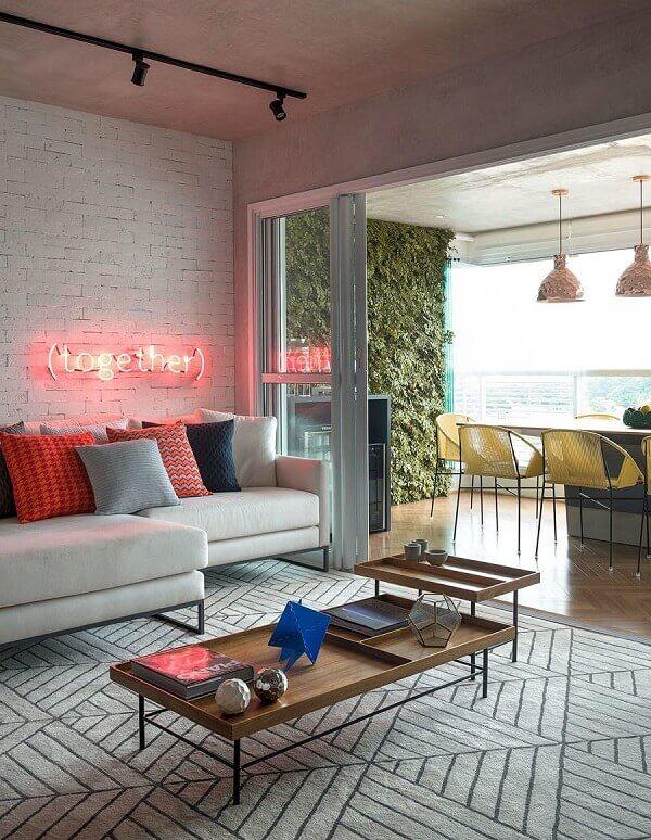 As letras decorativas em neon trazem destaque para a parede