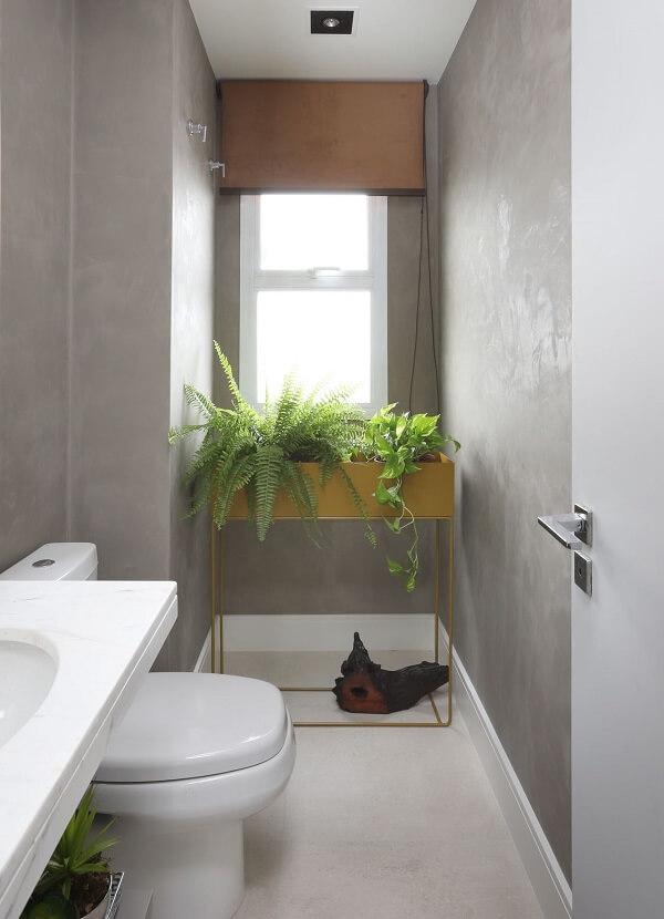 Banheiro compacto com parede de cimento queimado e bancada de granito
