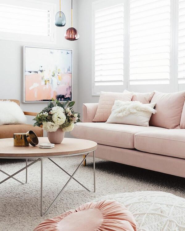 Sala de estar com sofá rosa e quadro abstrato