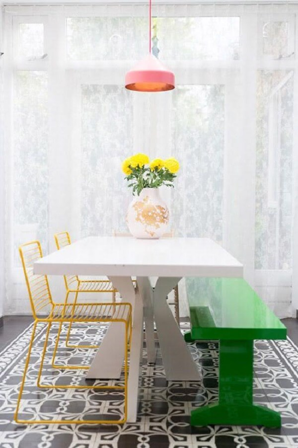Cadeira amarela com design minimalista conversa com o design arrojado do banco verde