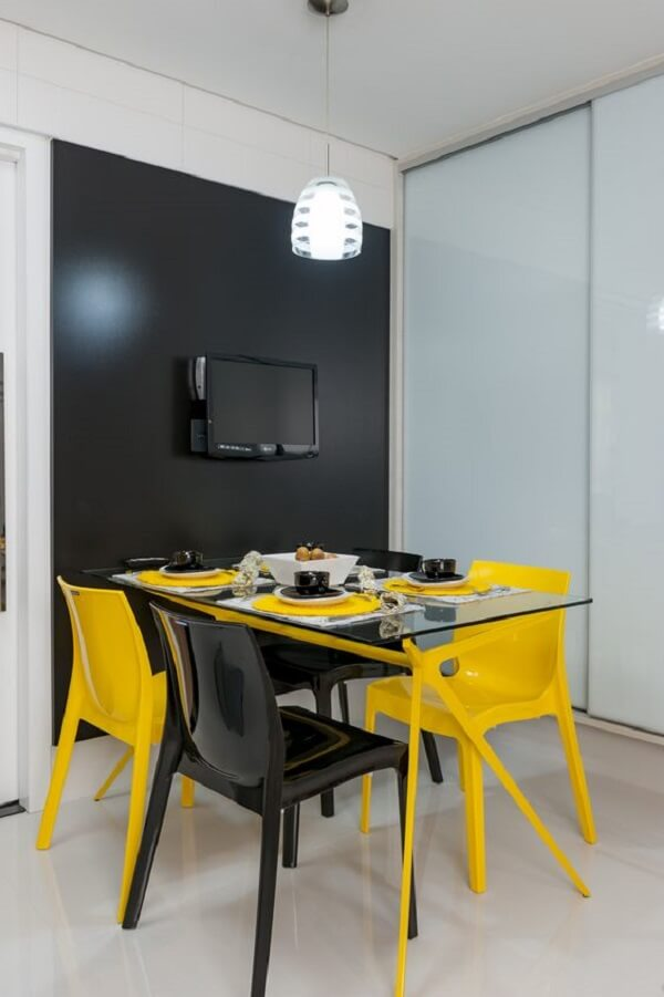 Cadeira amarela e preta se misturam na mesa de jantar