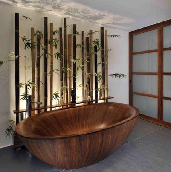 Cerca de bambu na parede compõe a decoração desse banheiro