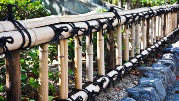 Cerca de bambu pequena amarrada com cordas em tom preto