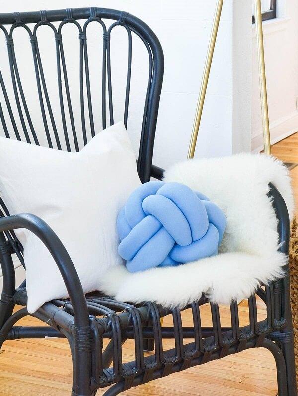 A almofada de nó em tom azul se destaca sobre a cadeira