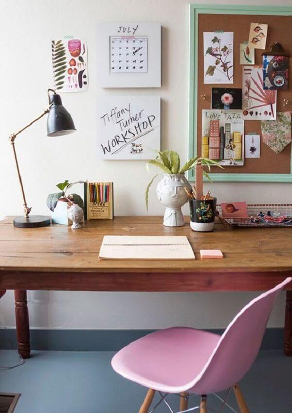Decoração minimalista com mesa de madeira e quadro de cortiça na parede