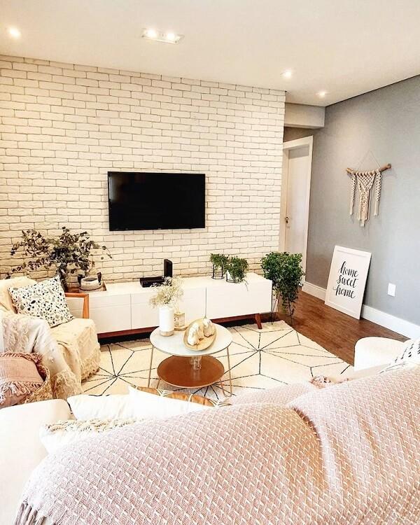 Decoração aconchegante com mantas, almofadas e tapete estampado. Fonte: Elas Duas Decoram