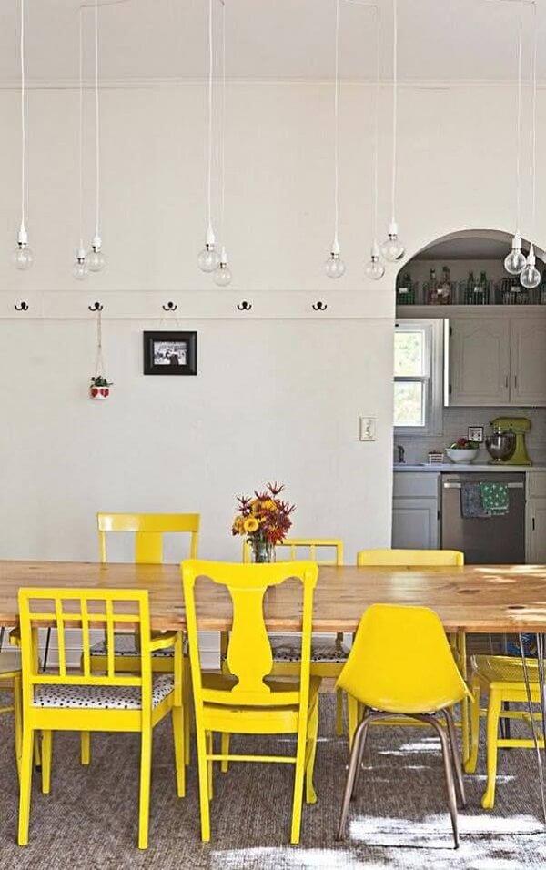 Diferentes modelos de cadeira amarela iluminam a mesa da sala de jantar