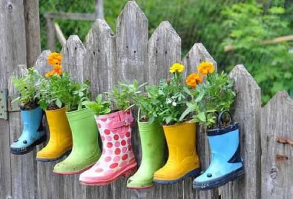 Enfeites para jardim feitos com botas fixadas na parede de madeira