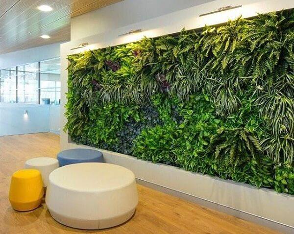 Escritório com parede revestida por um jardim vertical artificial traz aconchego aos funcionários
