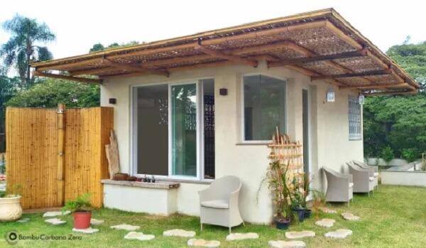 Casa pequena com cerca de bambu na parte externa