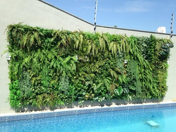 Parede da piscina com jardim vertical com flores artificiais