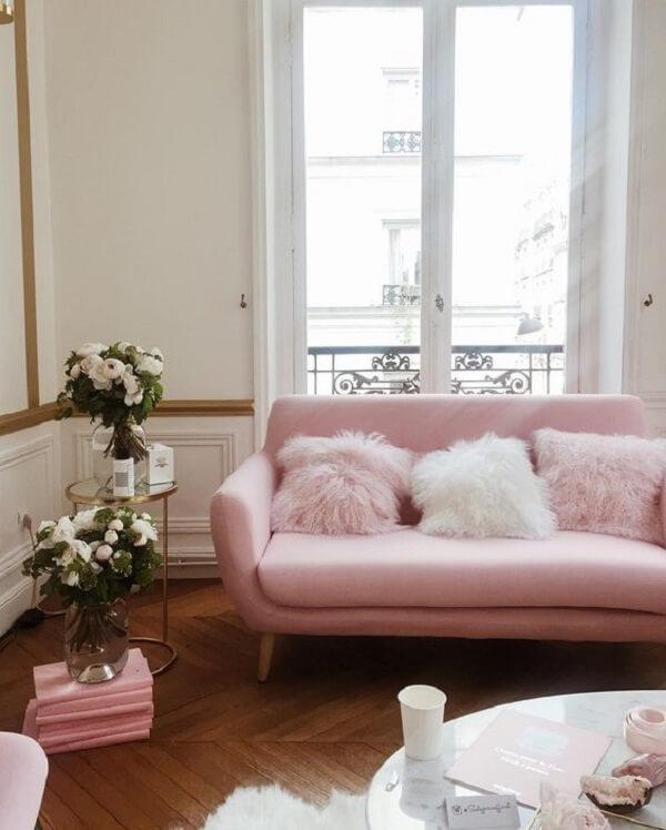 Sofá rosa com almofadas felpudas encantam a decoração do ambiente