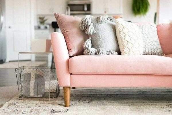 Sofá rosa com pé de madeira e almofadas neutras