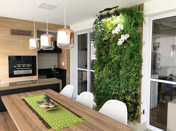 Varanda com mesa de madeira e jardim vertical com flores artificiais