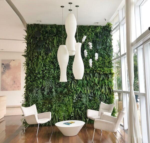 A parede revestida com jardim vertical artificial trouxe cor ao ambiente