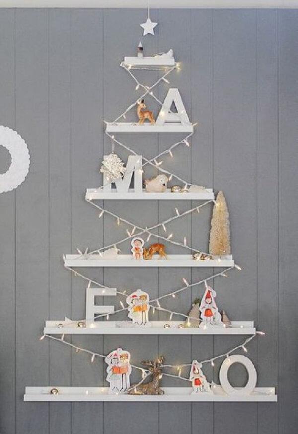 Árvore de Natal na parede feita com prateleiras brancas