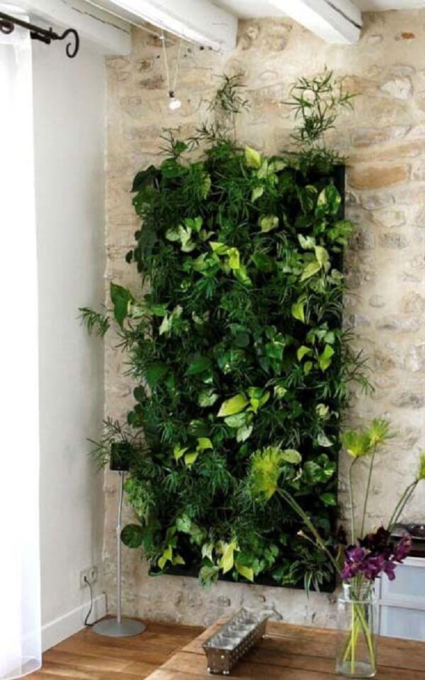 Parede de tijolinho aparente e jardim vertical artificial