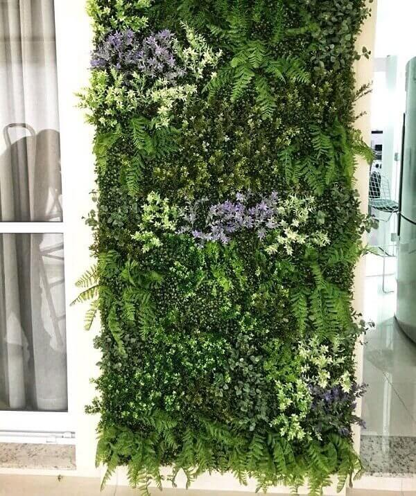 Jardim vertical artificial com flores fixada na varanda