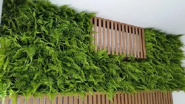 Jardim vertical artificial feito com samambaias esconde ar condicionado