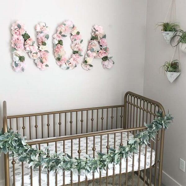 Letras decorativas com flores se conectam com os demais elementos do quarto do bebê