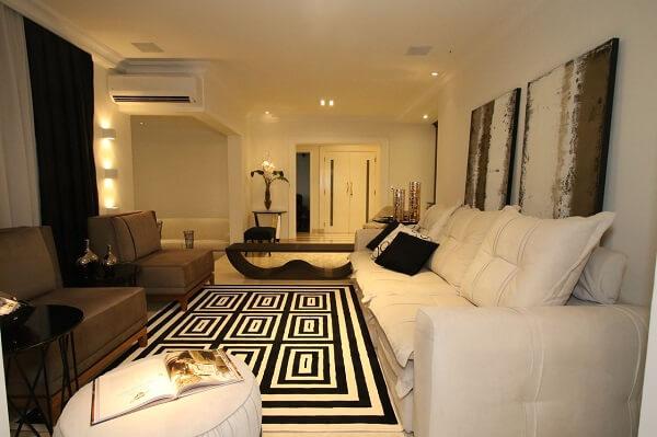 Living com sofá de três lugares e tapete geométrico preto e branco
