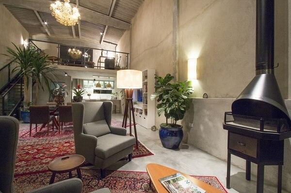 Loft super charmoso decorado com tapete estampado e poltrona cinza