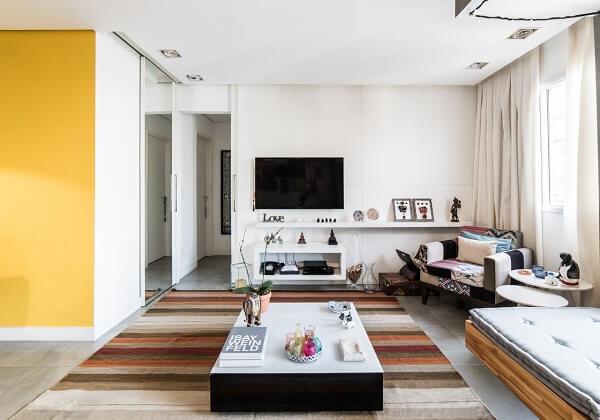 Móveis claros, tapete listrado e poltronas para sala de tv