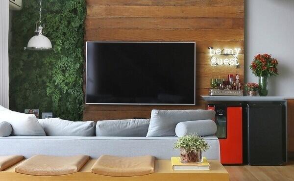 O jardim vertical com flores artificiais decora o ambiente da sala de estar