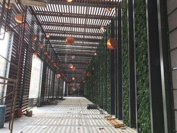 O jardim vertical com flores artificiais foi fixado na parede desse ambiente.