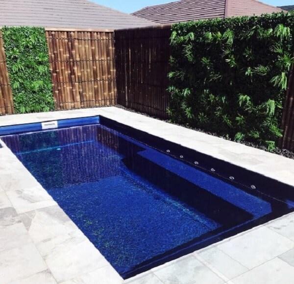 O jardim vertical e a cerca de bambu encantam a decoração da piscina