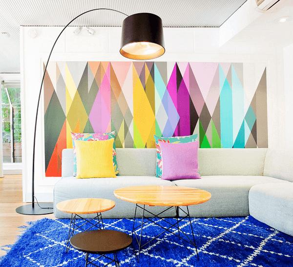 Painel colorido, mesa de centro de madeira e tapete geométrico azul