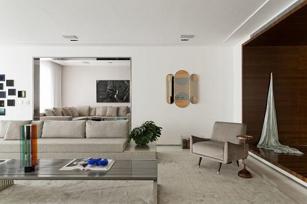 Poltrona cinza claro aveludada decora o ambiente dessa residência