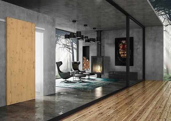 Poltronas de couro e parede de cimento queimado decoram o ambiente