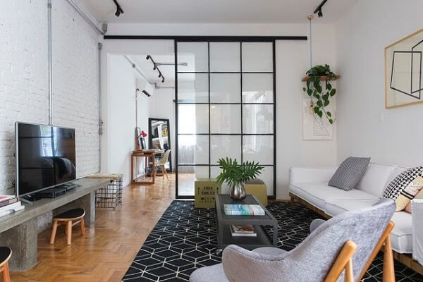 Poltronas para sala de tv e porta de correr de vidro encantam a decoração do espaço